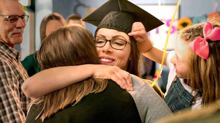 Jackie wearing graduation cap hugging family