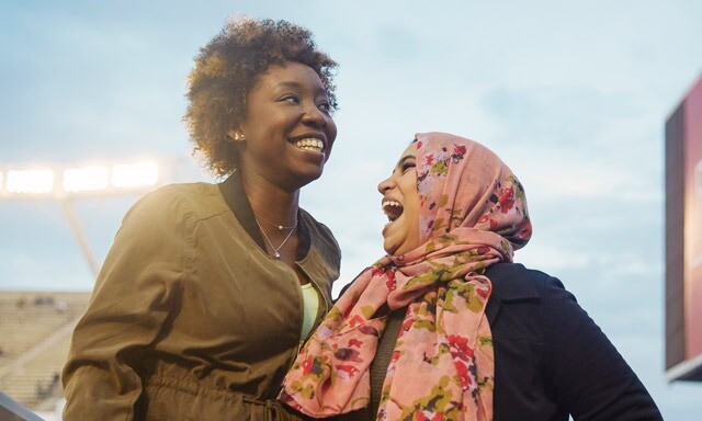 A black woman and a Muslim woman wearing a head scarf stand close to each other, smiling and laughing.
