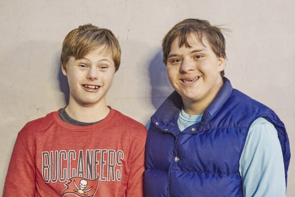 Two young white boys with Downs Syndrome stand close together against a concrete wall, smiling happily.