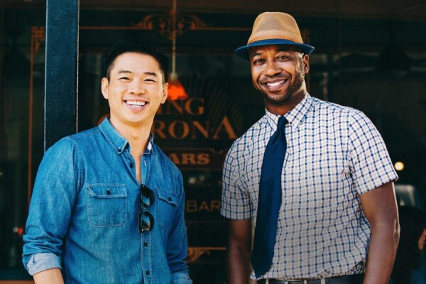 An Asian man and Black man stand next to each other, smiling