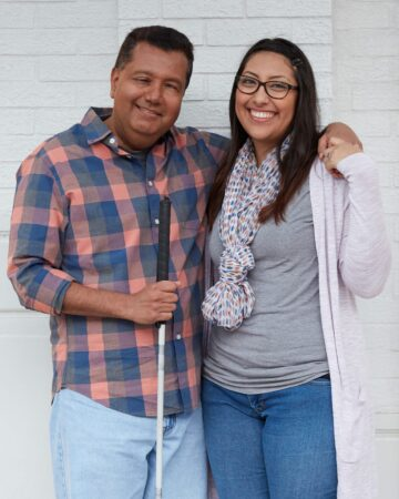 A man holding a support cane has his arm around a young woman. They are holding hands and smiling.