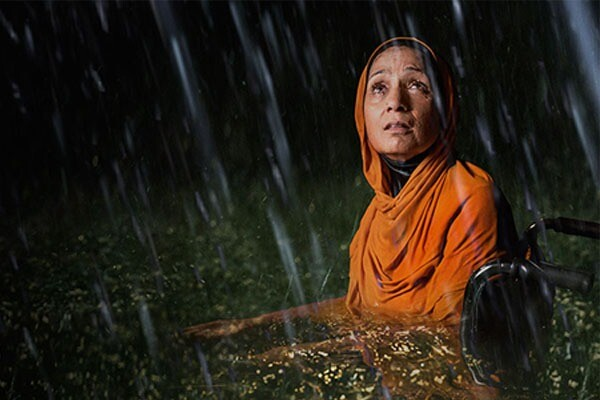 A Muslim woman in a wheelchair surrounded by flood waters.