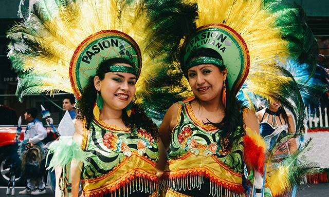 Two smiling Bolivian women wearing elaborate green, yellow, and red costume dresses and feathered headdresses that say Pasion Boliviana.