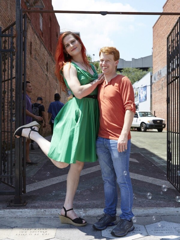 A trans woman and man stand in an alley, smiling and posing playfully for the camera.