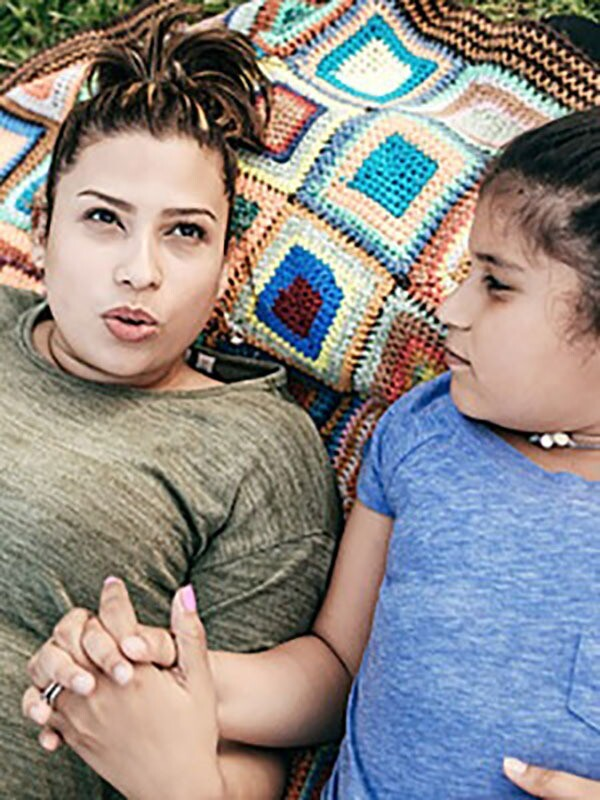 A mother and daughter hold hands while lying on a blanket in the grass having a thoughtful discussion.