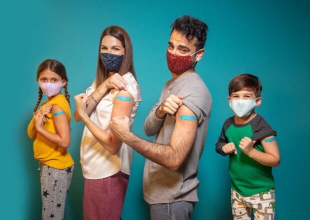 Familia con máscaras con tiritas en los brazos